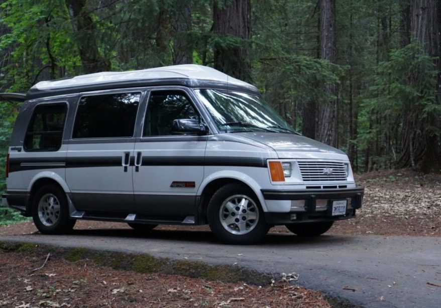 A van sits in the middle of the woods.