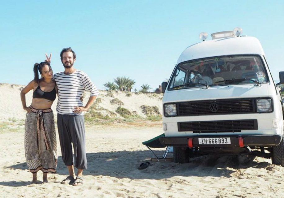 standing next to van on beach