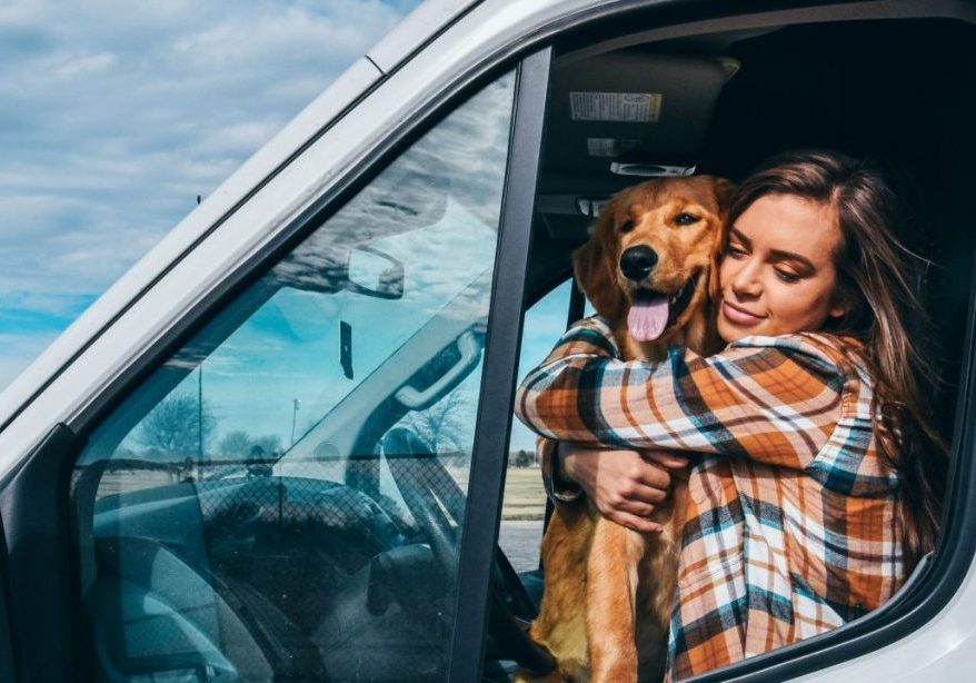girl and dog hugging on driver seat of van